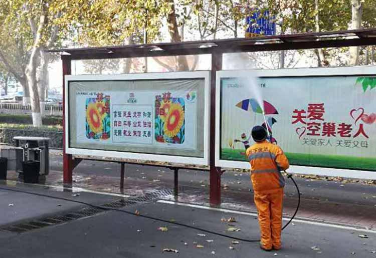 高压清洗车在冲洗公交站牌