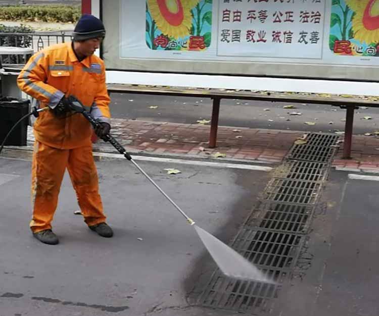 高压清洗车在冲洗下水道井盖
